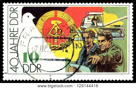 STAVROPOL RUSSIA - APRIL 28 2016: a stamp printed by GDR shows Harvestler and farmers 40 years of the GDR circa 1989