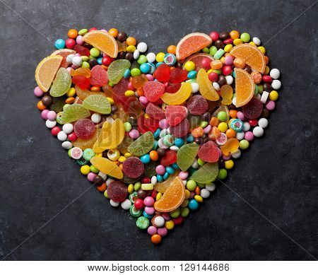 Colorful candies, jelly and marmalade heart on stone background. Top view
