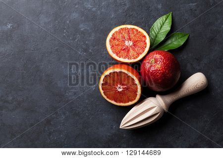 Red oranges and juicer on stone background. Top view with copy space