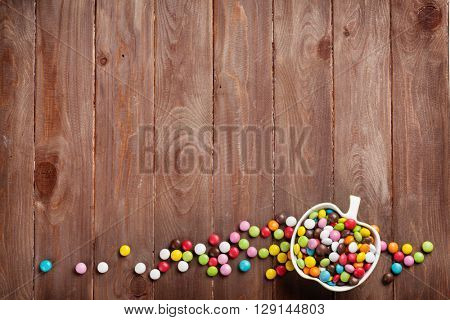 Colorful candies over wooden background. Top view with copy space