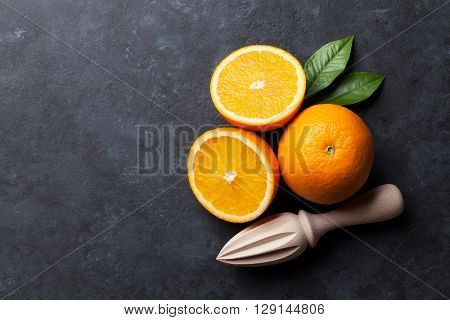 Oranges and juicer on stone background. Top view with copy space