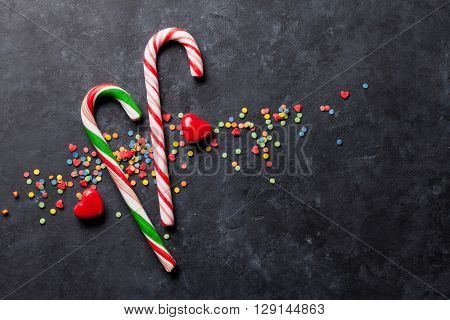 Candy canes and heart candies over stone background. Top view