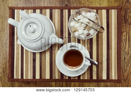 Top view of a cup of tea teapot and sugar bowl on a wooden background