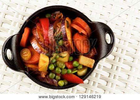 Delicious Homemade Colorful Vegetables Ragout with Eggplant Carrots Potatoes Leek Red Bell Pepper and Green Pea in Black Iron Stewpot closeup on Wicker background. Top View