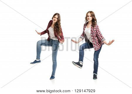 two young beautiful happiness women dancing over white background