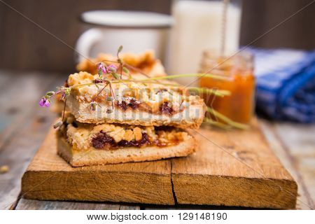 some pieces of pie with apricot jam and milk on wooden plate