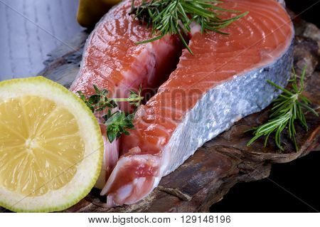 Delicious Raw Salmon Steak with Slice of Lemon and Rosemary closeup on Shale Stone Board