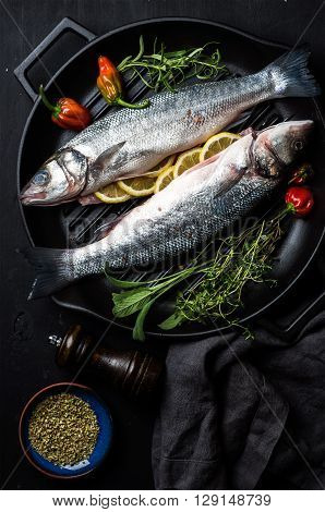 Raw uncooked seabass fish with herbs and spices in cast iron cooking pan on black wooden background. Top view, dark consept