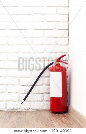 Fire extinguisher near white wall ready for use