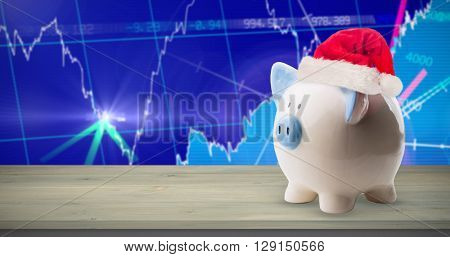 Image of money-box with Christmas hat against stocks and shares