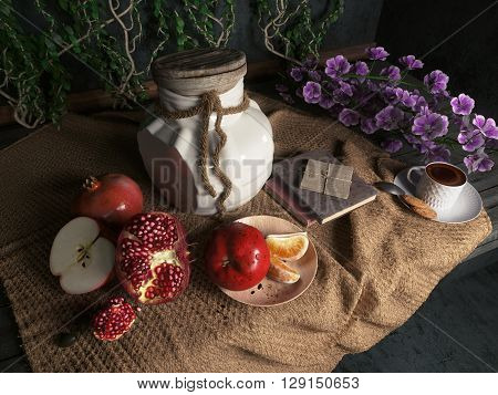 jar,apples,pomegranate,coffe cup with books and orange on canvas drapery conceptual still-life