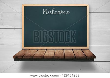Welcome message against blackboard on a wooden shelf
