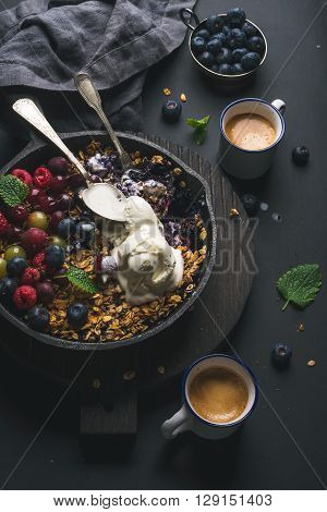 Healthy breakfast. Oat granola crumble with fresh berries, seeds and ice-cream in iron skillet pan on dark wooden board and cups of coffee over black backdrop, top view, vertical