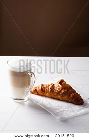 Glass of latte macchiato and French croissant on baking paper. Vertical scene on white wooden background.
