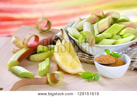Peeled and chopped raw rhubarb prepared for cooking compote with brown sugar and lemon, in the background other rhubarb stalks in soft focus