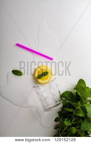 Overturned glass of homemade lemonade with mint.
