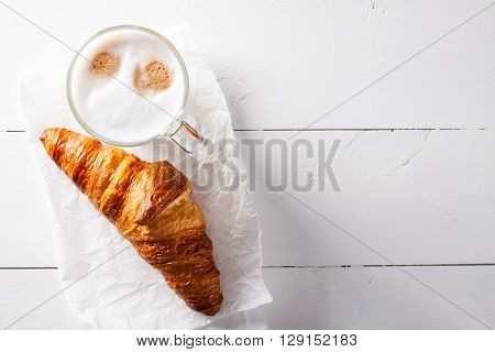 Glass of latte macchiato and French croissant on baking paper. Flat lay on white wooden background.