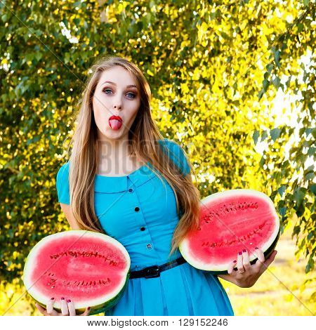 Beautiful blonde girl in a blue dress with long hair holding two halves of a sliced watermelon and shows tongue