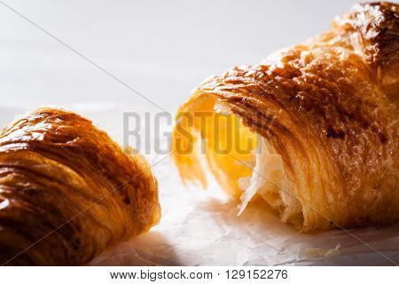 Tear off a piece of French pastry Croissant on white baking paper.