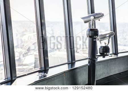 Telescopes overlooking a city on an observation deck at a high tower