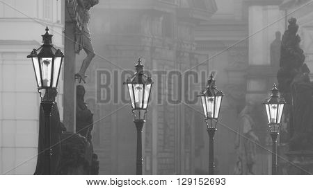 Street lamps on Charles bridge illuminated by morning sun and dark silhouettes of statues, Prague, Czech Republic. Black and white image.
