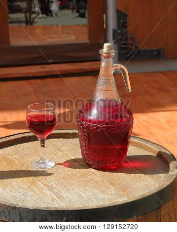 The picture shows a jug of red wine. Next poured a glass of wine. Both items placed on a barrel of wine.