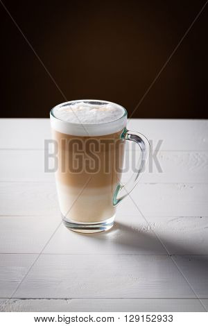 Original latte macchiato coffee in transparent glass on white wooden background.