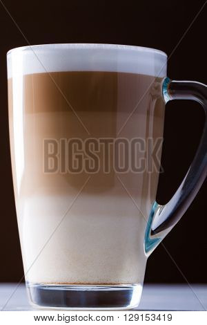 Original latte macchiato coffee in transparent glass.