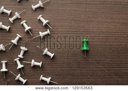 bright green push pin out of the crowd concept
