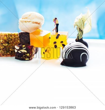 Dessert menu template, love concept card with kissing couple and sweets. Man and woman figures, desserts on white and blue background. Colorful candies, marmalade, physalis chocolate, nuts.