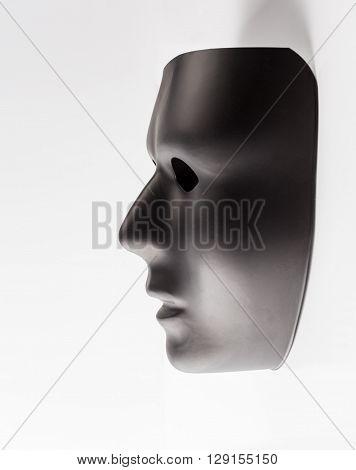 Black Mask Emerging From White Background