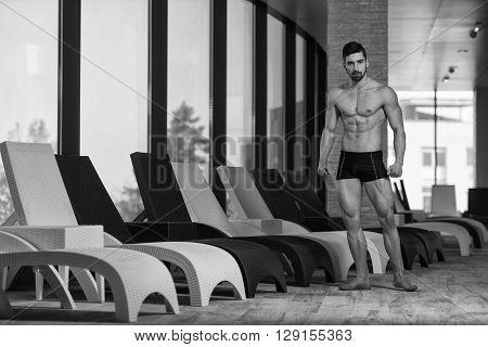 Young Man Flexing Muscles At Sun Lounger