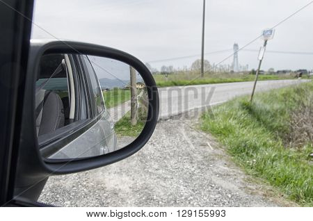 Country road seen from the rearview mirror