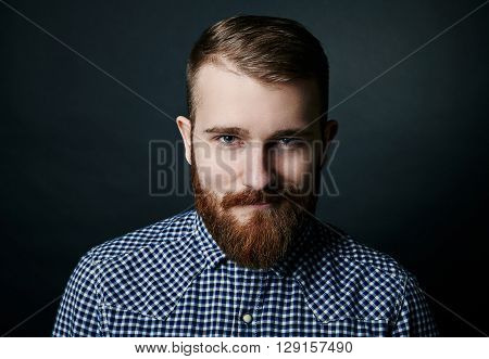 Smiling red bearded handsome stylish man in blue checkered shirt, close up studio portrait on dark background