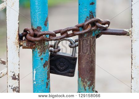 Closed gates with padlock and iron chain. metallic textures, shabby turquoise paint surface. macro view. Security concept with closed iron gate, vintage lock