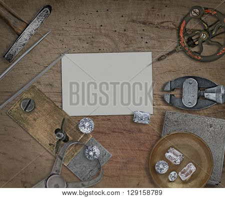 vintage jeweler tools and diamonds over wooden bench blank card for your business