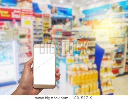 Hand with smartphone white screen on blurred in pharmacy background