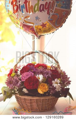 Flowers in the basket, balloon with happy birthday text and candles, on wooden background