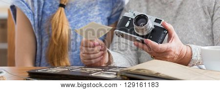 Cropped picture of an elder woman holding a camera and showing old photographs to her granddaughter