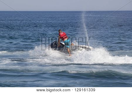 CAMYUVA KEMER TURKEY - JULY 16 2015: Unidentified Turkish man glides over the waves of the Mediterranean Sea on Jet Ski. Extreme water sports are increasingly popular on the beaches of Turkey
