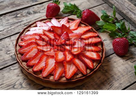 Homemade traditional strawberry tart with mint leaves on vintage wooden background