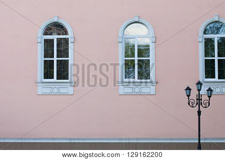 Street lamp post against pink wall. Facade building with retro style windows design