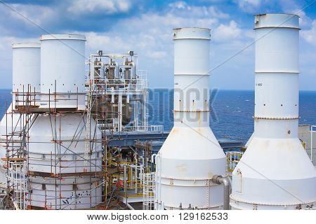 Gas exhaust of gas compressor at top deck with scaffolding of oil and gas processing platform