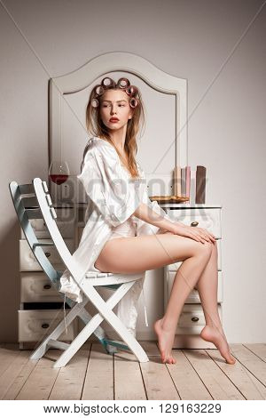 Pretty young woman in a dressing-gown and curlers sitting near the vanity table