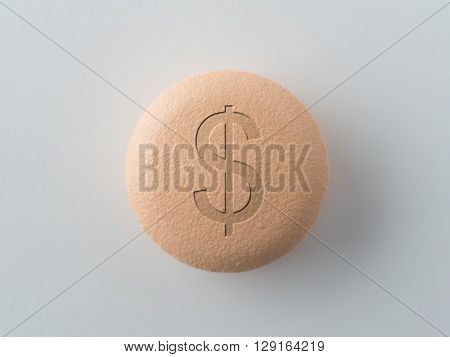 Pharmaceutical industry or Big Pharma. A tablet or pill with a dollar mark, isolated on natural white. Shallow depth of field due to subject size.