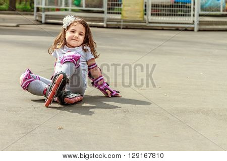 young girl in protective equipment and rollers stands on walkway in park, outdoor portrait