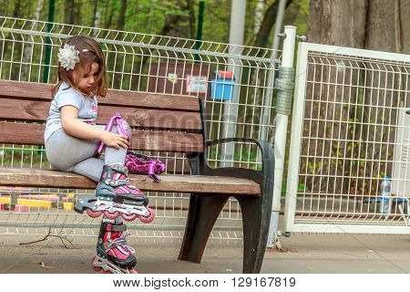 young girl in protective equipment and rollers in park, outdoor portrait