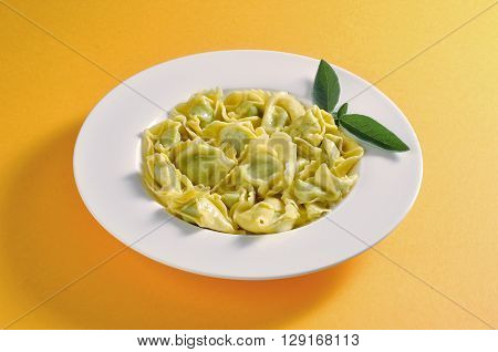 Dish with portion of ravioli with butter and sage
