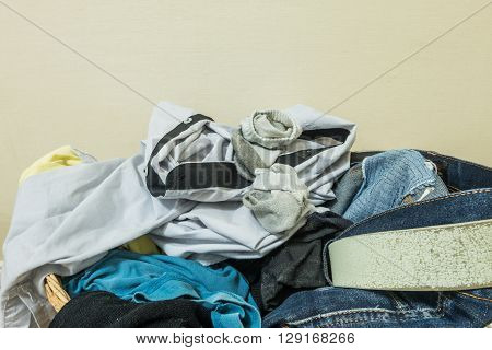 Closeup used clothes in wood basket at corner in room