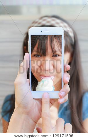 Hand man with Smartphone taking a picture of Asia girl child eat ice cream in restaurant.